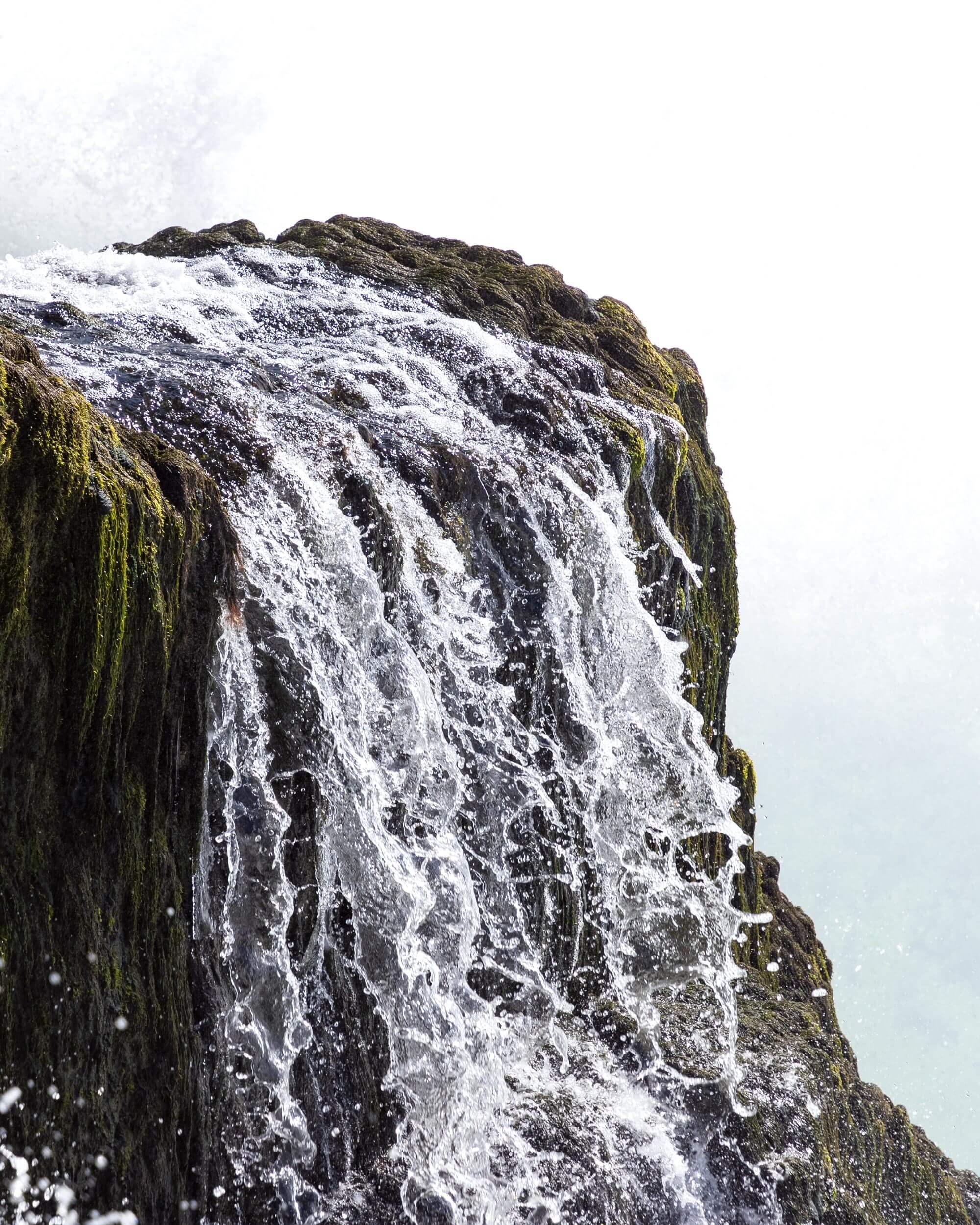 Kleiner Wasserfall fliesst über einen Felsen hinab Themenbild Old Donald's Schale Kokosnuss rund goldiger Rand Behälter für Grinder Inhalt Cbuy.ch Alles Gute aus Cannabis Schweizer CBD Hanfblüten CBD Produkte CBD Öle Hanf-Lebensmittel Schlafen Schmerzen Entspannung Natur SWISS Gate AG